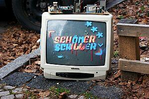 Ein Fernseher mit aufgesprühtem Logo von SCHÖNERSCHILLER