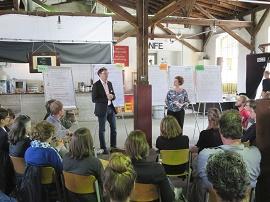 Moderator und Workshopteilnehmende vor Flipcharts