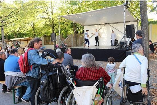 Zuschauer mit und ohne Behinderung beim Bühnenprogramm des Kiezfests.   Foto: QM Rollbergsiedlung
