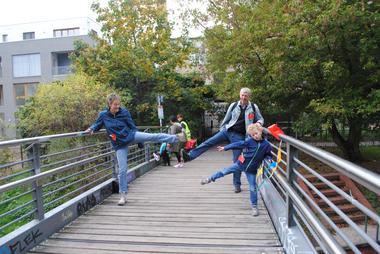 Eine Familie macht Bewegungsübungen auf einer Brücke.