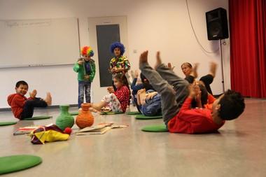 Kindergartenkinder turnen auf dem Boden.