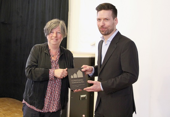 Die Senatorin für Stadtentwicklung und Wohnen überreicht Robby Schönrich, Geschäftsführer der Fabrik Osloer Straße, die Plakette der Städtebauförderung. Bild: D. Hensel